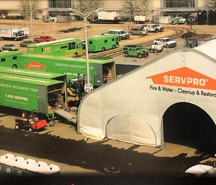 Retail stores in a parking lot with SERVPRO vehicles