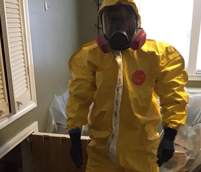 Our crew member wearing proper PPE during a mold remediation job: gloves, respirator, boot covers, full body suit.